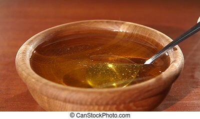 Taking honey by metal spoon in wooden bowl, slow motion -...