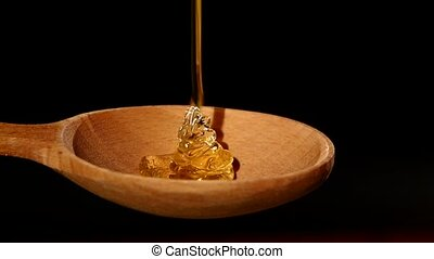 Honey dripping from a wooden honey dipper on black, slow...