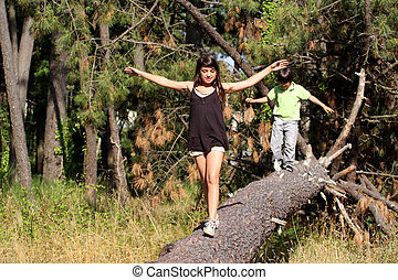 Girl walking across log in a forest in summer