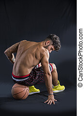 Young athletic man sitting on basketball ball
