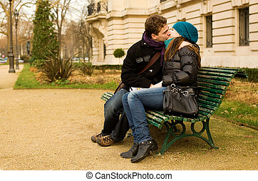 Young couple in love kissing on a bench