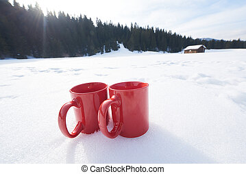 two red coups of hot tea drink in snow at winter - two red...