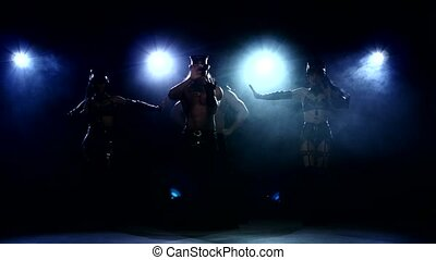 Stripease policeman: four person dancing on dark. silhouette...