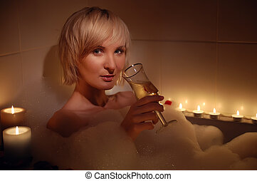 nude woman in foamy bath with petals of roses and by light...