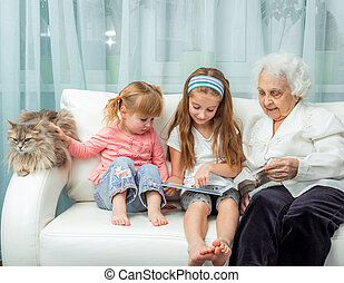 elderly woman with granddaughters reading book