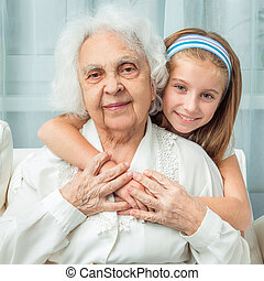 little girl embracing grandmother - smiling little girl...