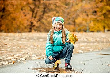 pretty little girl squatting with leaves in hand -...