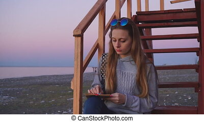 Travel: beautiful girl tourist drawing sunset at the beach...