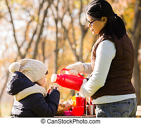 A little kid holding a cup while her mother pouring tea -...