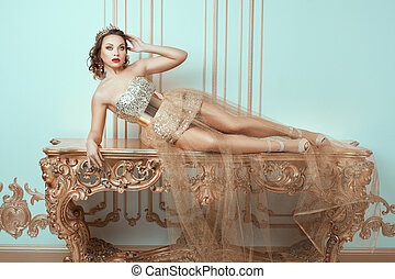 Fashionable woman lies on an expensive antique table She is...