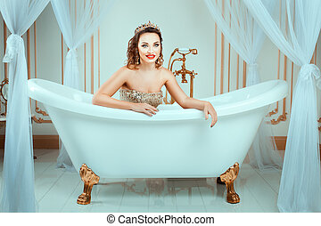Girl with crown lies in the bath and smiling Her bright...