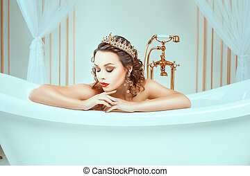 Beautiful naked young woman sitting in expensive jewelry...