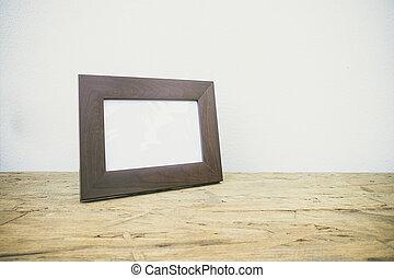 Vintage photo frame on wooden table over grunge background,...