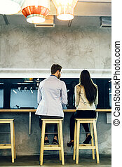 Man talking to a woman while sitting in a bar