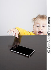 baby trying to take phone on table - portrait of blonde...