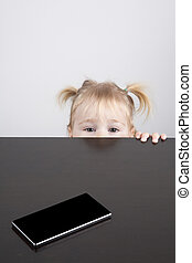 baby watching camera and phone on table - portrait of blonde...