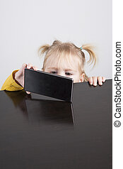 baby watching phone on table - portrait of blonde caucasian...