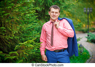 young man with a jacket over his shoulder in park