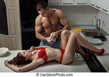 Girl lies on the kitchen table, a man prepares dough She is...