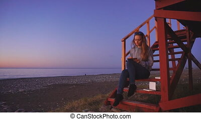 Travel: beautiful girl tourist drawing sunset at the beach....