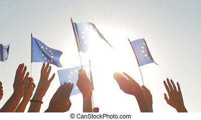 People with raised hands waving flags of the European Union...