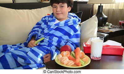 Cute young boy eating cucumber - Cute child lying on a couch...