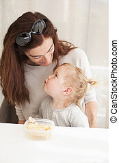 baby eating and looking mother - portrait of two years age...