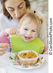 baby eating rice from tupperware - portrait of two years age...