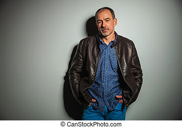 old casual man in leather jacket an jeans standing with...