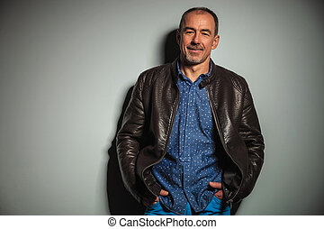 smiling old casual man in leather jacket with hands in...