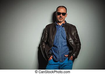 cool old casual man wearing leather jacket and sunglasses...