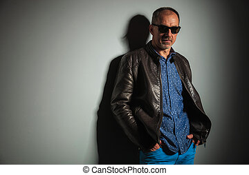 side view of a mature casual man in leather jacket and...