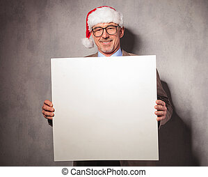 smiling santa claus business man holding a blank board in...