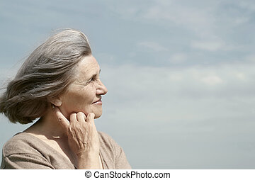 elderly woman posing against the sky