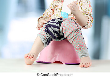 Childrens legs hanging down from a chamber-pot on a blue...
