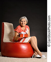 Happy elderly woman sitting with gift