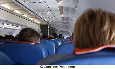 Interior of airplane with passengers on seats. - Interior of...