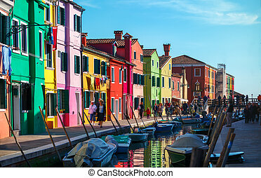Bright coloured houses on coast of channel in Burano island...