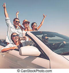 ENjoying friendly trip. Group of young happy people enjoying road trip in their white convertible and raising their arms up