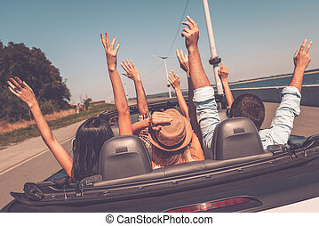 Enjoying road trip. Rear view of young happy people enjoying road trip in their convertible and raising their arms up