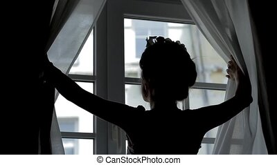 Girl looks out the window. Woman opens curtains and looking...