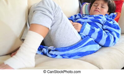 Child with bandage on leg, laying - Child foot wrapped with...