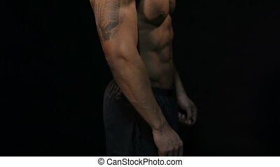 Man posing on a black background, shows his muscles....