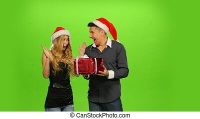 young man giving a Christmas present to his surprised girlfriend. green screen