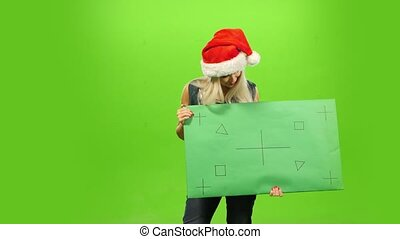 Beautiful blonde woman in Santa hat, New Year, green screen, blank sign