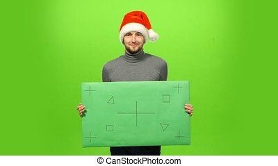 Happy handsome brutal man in Christmas hat. green screen, blank sign