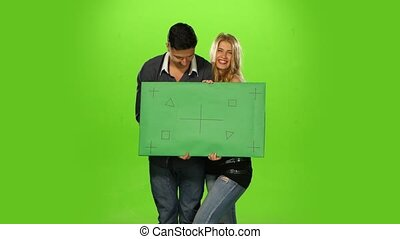 energetic and beautiful Couple holding up a blank sign,...