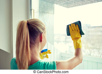happy woman in gloves cleaning window with rag - people,...