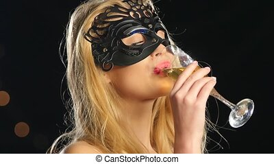 blonde woman with venetian mask and glass of champagne, on black, bokeh