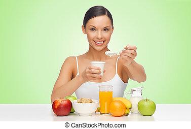 happy woman eating yogurt for breakfast - people, healthy...